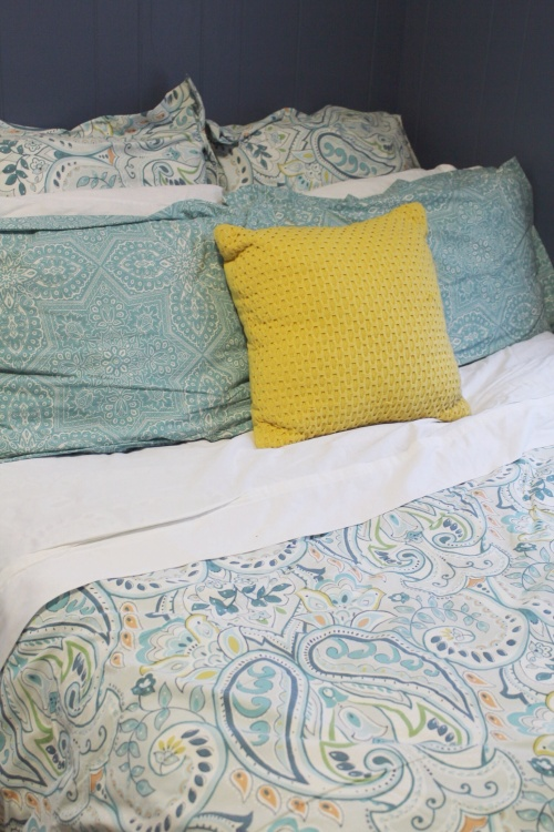 teal, yellow, and green bedding with moody navy walls.